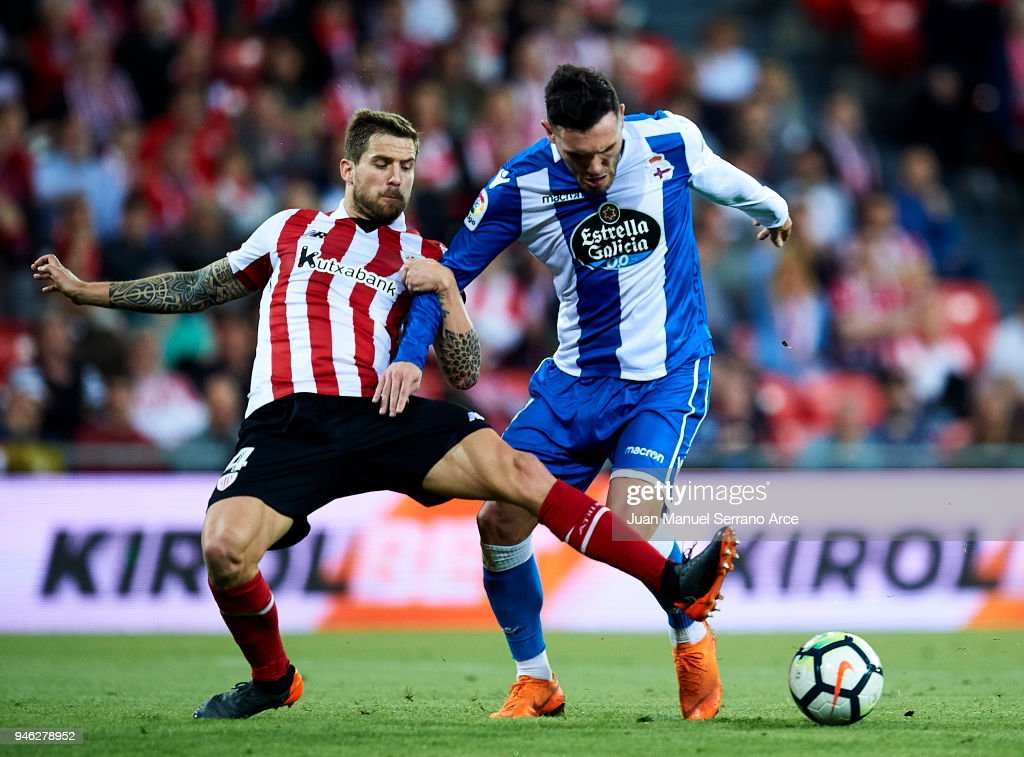 Lucas Perez of RC Deportivo La Coruna competes for the ball with Inigo Martinez of Athletic Club during the La Liga match between Athletic Club Bilbao and RC Deportivo La Coruna at San Mames Stadium on April 14, 2018 in Bilbao, Spain.