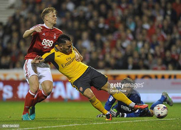 Lucas Perez scores Arsenal's 3rd goal his 2nd under pressure from Matt Mills of Nottingham Forest during the match between Nottingham Forest and...