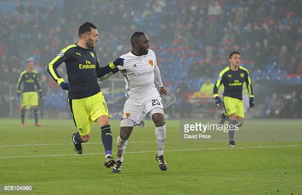 Lucas Perez scores his and Arsenal's 3rd goal under pressure from Eder Balanta of Basel during the UEFA Champions League match between FC Basel and...