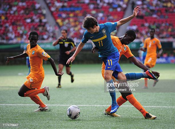 Lucas Piazon of Brazil is tackled by Mory Kone and Ibrahim Bah of Ivory Coast during the FIFA U-17 World Cup Group F match between Ivory Coast and...