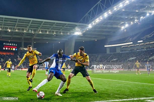 Lucas Possignolo and Henrique Gelain Custodio of Portimonense SC compete for the ball with Moussa Marega of FC Porto during the Liga Nos match...