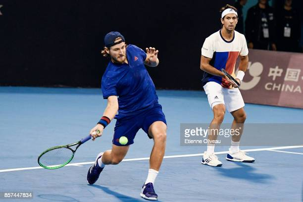 Lucas Pouille of France and Fernando Verdasco of Spain in action during their Men's double first round match against Jack Sock and John Isner of the...