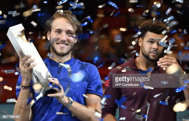 Lucas Pouille of France holds the trophy after winning against JoWilfried Tsonga of France in their men's singles final match during the ATP...