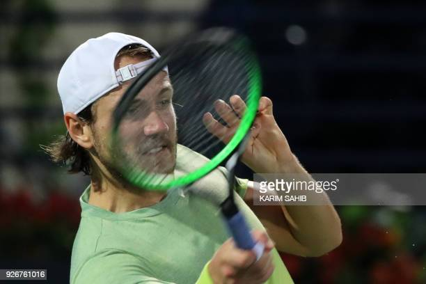 Lucas Pouille of France returns the ball to Spain's Roberto Bautista Agut during their final match in the 2018 ATP Dubai Duty Free Tennis...