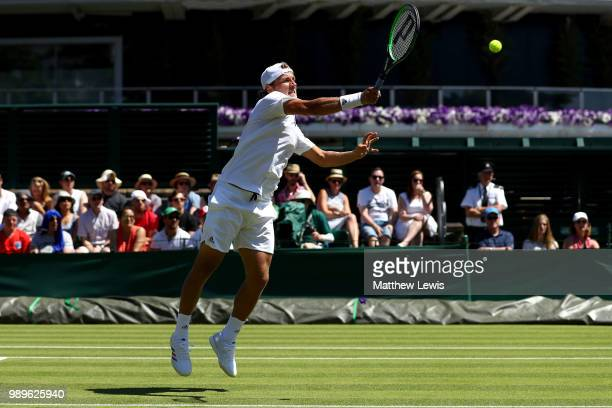 Lucas Pouille of France returns to Denis Kudla of The United States during their Men's Singles first round match on day one of the Wimbledon Lawn...