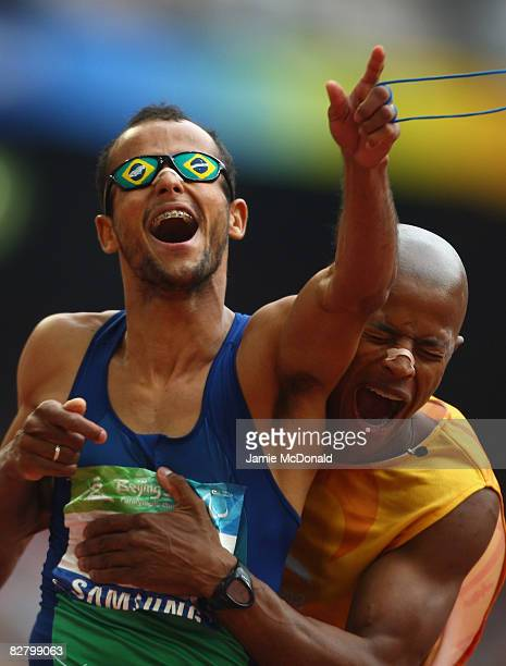 Lucas Prado of Brazil and his guide celebrate gold in the Men's 200m dash at the National Stadium during day seven of the 2008 Paralypic Games on...