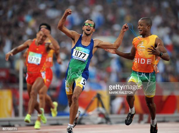 Lucas Prado of Brazil celebrates next to his guide after winning the final of the men's 100 metre T11 classification race at the 2008 Beijing...