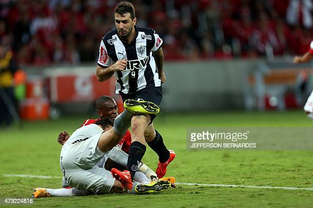 Lucas Pratto of Brazil's Atletico Mineiro vies for the ball with Allison goalkeeper of Brazil's Internacional during their Copa Libertadores football...