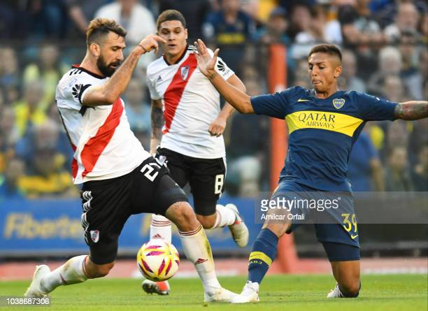 Lucas Pratto of River Plate and Agustín Almendra of Boca Juniors compete for the ball during a match between Boca Juniors and River Plate as part of...