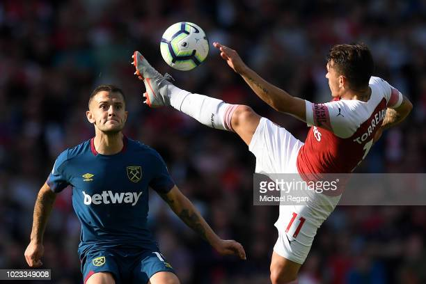 Lucas Torreira of Arsenal controls the ball as Jack Wilshere of West Ham United looks on during the Premier League match between Arsenal FC and West...
