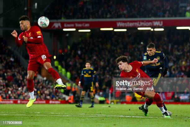 Lucas Torreira of Arsenal has a shot blocked by Alex OxladeChamberlain of Liverpool during the Carabao Cup Round of 16 match between Liverpool and...