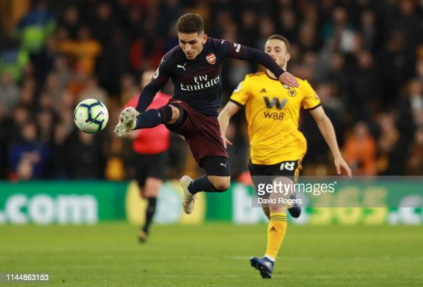 Lucas Torreira of Arsenal stretches for the ball under pressure from Diogo Jota of Wolverhampton Wanderers during the Premier League match between...