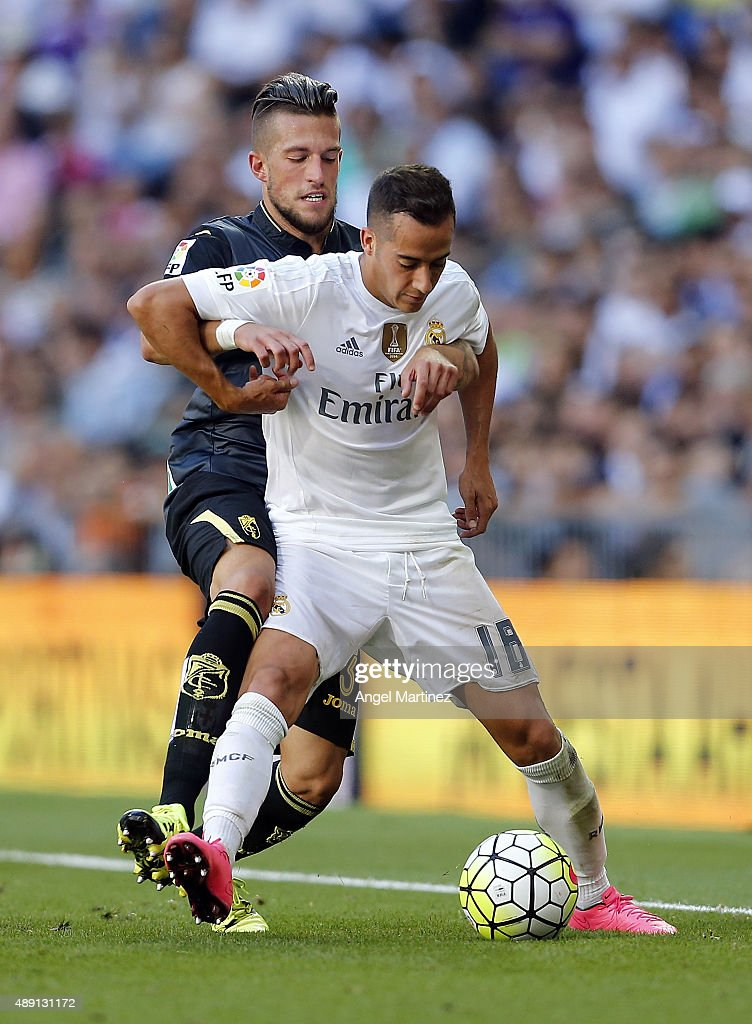 Lucas Vazquez of Real Madrid competes for the ball with Cristiano Biraghi of Granada CF during the La Liga match between Real Madrid CF and Granada CF at Estadio Santiago Bernabeu on September 19, 2015 in Madrid, Spain.