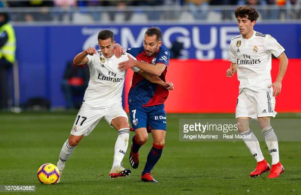Lucas Vazquez of Real Madrid competes for the ball with David Ferreiro of SD Huesca during the La Liga match between SD Huesca and Real Madrid CF at...
