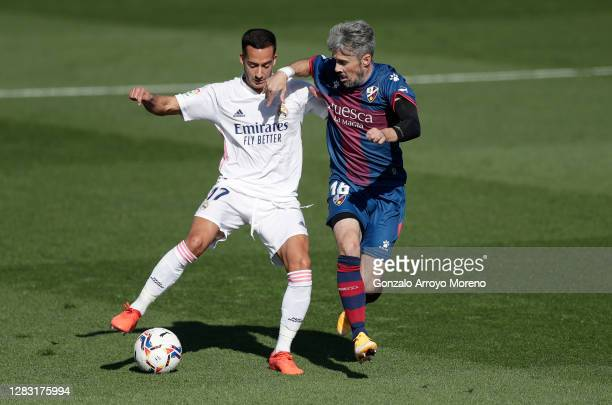 Lucas Vazquez of Real Madrid is challenged by Luisinho of SD Huesca during the La Liga Santander match between Real Madrid and SD Huesca at Estadio...