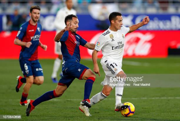 Lucas Vazquez of Real Madrid is chased by David Ferreiro of SD Huesca during the La Liga match between SD Huesca and Real Madrid CF at Estadio El...