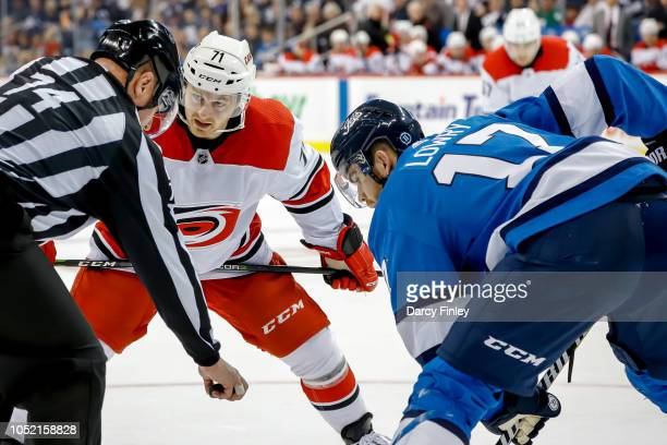 Lucas Wallmark of the Carolina Hurricanes and Adam Lowry of the Winnipeg Jets get set for a third period faceoff at the Bell MTS Place on October 14...