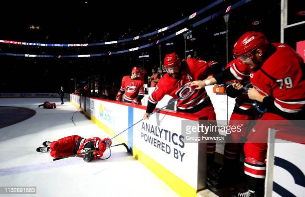 Lucas Wallmark of the Carolina Hurricanes participates in the Storm Surge with teammates Micheal Ferland and Justin Faulk during an NHL game against...