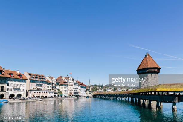 lucerne cityscape and chapel bridge on a sunny day with clear blue sky, - ルツェルン ストックフォトと画像
