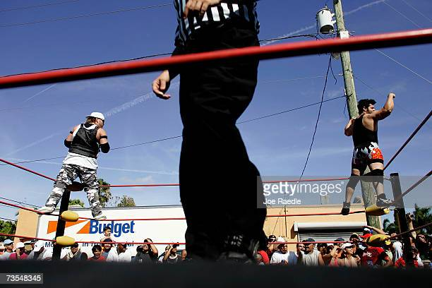 Lucha Libre wrestlers El Toro and El Monstruo wave to the crowd before their match during the annual Calle Ocho celebration March 11 2007 in Miami...