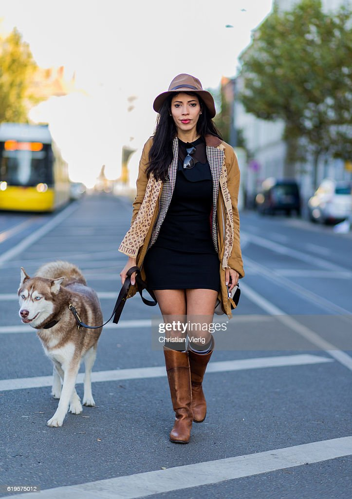 Lucia Amelia Pimentel with her husky dog wears a Louis Vuitton scarf, brown hat, beige wool coat, plaid jacket, black dress, socks and brown boots on October 31, 2016 in Berlin, Germany.