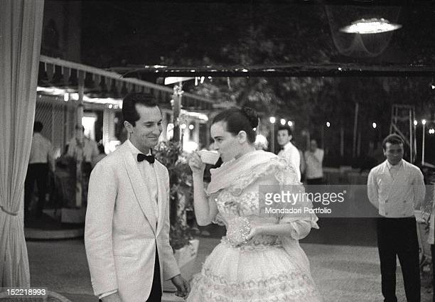 Lucia Bosè and his husband bullfighter Luis Miguel Dominguin are in a Venetian club both wear elegant evening dresses and Lucia Bosè sips something...