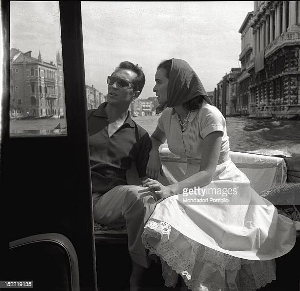 Lucia Bosè with her bullfighter husband Luis Miguel Dominguin are on a boat in the Venetian lagoon; they both are seated and watch Venetian palaces,...