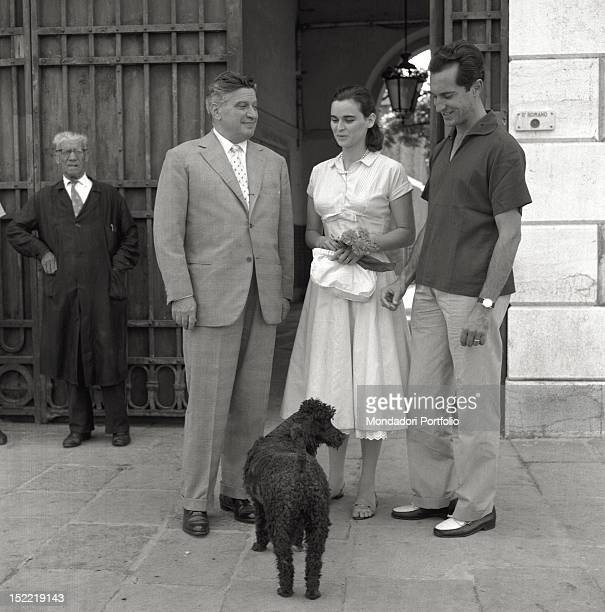 Lucia Bosè with her bullfighter husband Luis Miguel Dominguin talk with a man in front of the main door of a palace near them a poodle dog Venice 1956