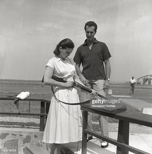 Lucia Bosè with her husband Luis Miguel Dominguin is in a shooting range the actress holds a rifle in her hand Venice 1956