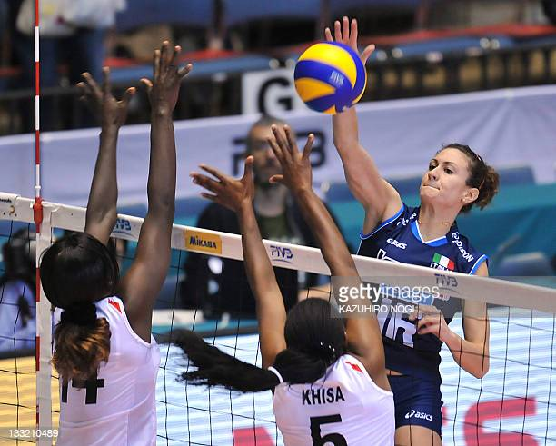 Lucia Bosetti of Italy spikes the ball over Kenyan players Mercy Moim and Diana Khisa during a match of the World Cup women's volleyball tournament...