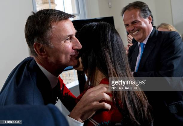 Lucia Hunt wife of Britain's Foreign Secretary Jeremy Hunt is kissed by her husband watched by Conservative MP Mark Field during Hunt's Conversative...