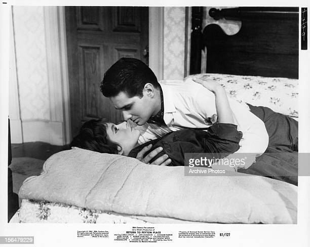 Luciana Paluzzi lying on the bed looking up at Brett Halsey as he moves closer to her for a kiss in a scene from the film 'Return To Peyton Place',...