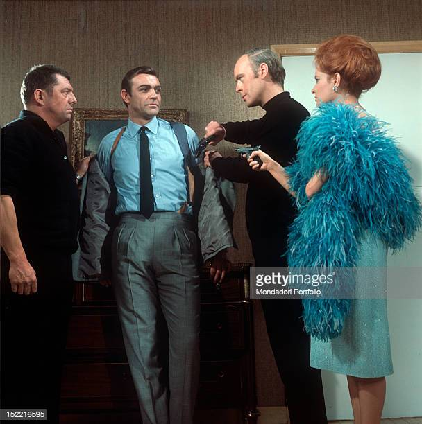 """Luciana Paluzzi, with two killers' aid, threatens Sean Connery at gun-point in a scene from """"Thunderball"""" by Terence Young, fourth episode of secret..."""