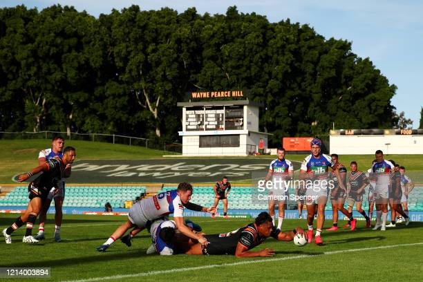 Luciano Leilua of the Wests Tigers scores a try during the round 2 NRL match between the Wests Tigers and the Newcastle Knights at Leichhardt Oval on...