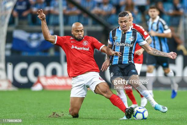 Luciano of Gremio battles for the ball against Rodrigo Moledo of Internacional during the match between Gremio and Internacional as part of...