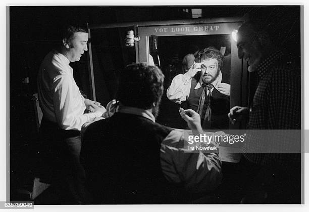 Luciano Pavarotti assisted by his dresser Joe Harris applies stage makeup while sitting in front of a mirror backstage at the San Francisco Opera...
