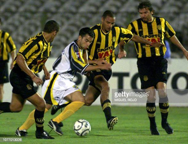 Luciano Roque a Venezuelan player for the Deportiva Tachira weaves the ball between the Penarol players Pilipauskas Barboza and De los Santos during...
