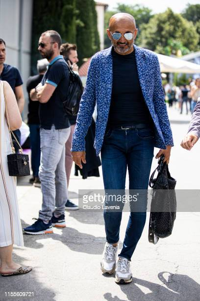 Luciano Spalletti wearing a blue tshirt blue floral print blazer blue jeans white sneakers and black bag is seen during Pitti Immagine Uomo 96 on...