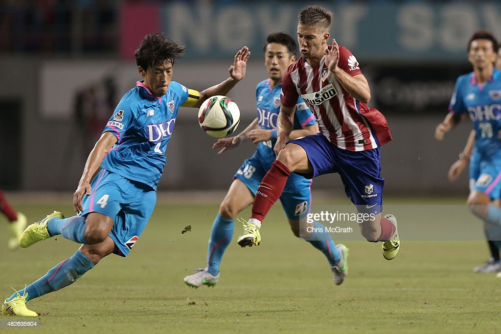 Luciano Vietto #23 of Atletico Madrid contests the ball with Teruaki Kobayashi #4 of Sagan Tosu F.C. during the friendly match between Atletico Madrid and Sagan Tosu F.C. at Tosu Stadium on August 1, 2015 in Tosu, Japan.