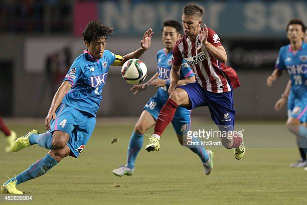 Luciano Vietto of Atletico Madrid contests the ball with Teruaki Kobayashi of Sagan Tosu F.C. During the friendly match between Atletico Madrid and...