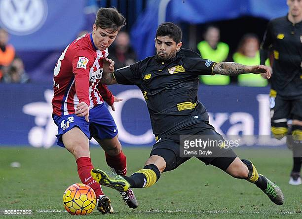 Luciano Vietto of Club Atletico de Madrid is tackled by Ever Banega of Sevilla FC during the La Liga match between Club Atletico de Madrid and...