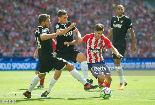 Luciano Vietto of Club Atletico de Madrid tried to beat Daniel Carrico of Sevilla FC during the La Liga match between Atletico Madrid and Sevilla at...