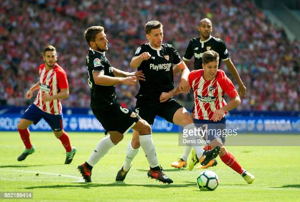 Luciano Vietto of Club Atletico de Madrid tries to beat Daniel Carrico of Sevilla FC during the La Liga match between Atletico Madrid and Sevilla at...