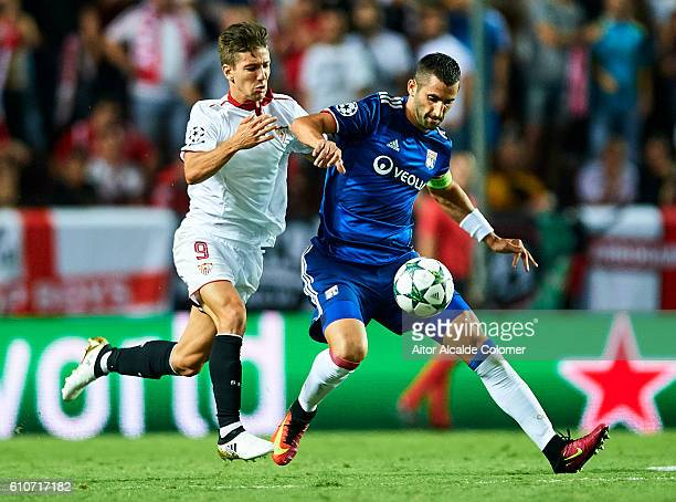 Luciano Vietto of Sevilla FC competes for the ball with Maxime Gonalons of Olympique Lyonnais during the UEFA Champions League match between Sevilla...