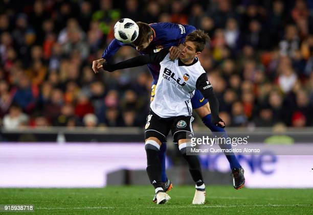 Luciano Vietto of Valencia competes for the ball with Gerard Pique of Barcelona during the Copa de Rey semifinal second leg match between Valencia...