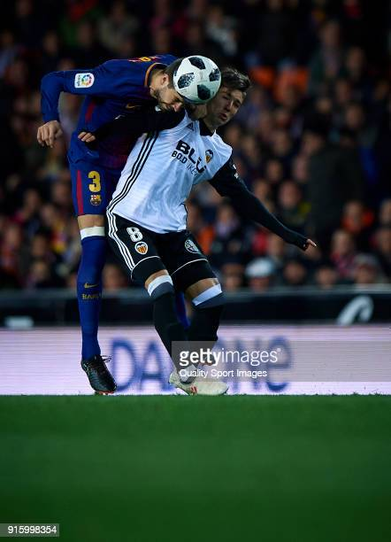 Luciano Vietto of Valencia competes for the ball with Gerard Pique of Barcelona during the Semi Final Second Leg match of the Copa del Rey between...