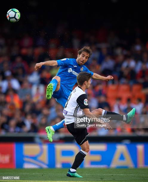 Luciano Vietto of Valencia competes for the ball with Mathieu Flamini of Getafe during the La Liga match between Valencia and Getafe at Mestalla...
