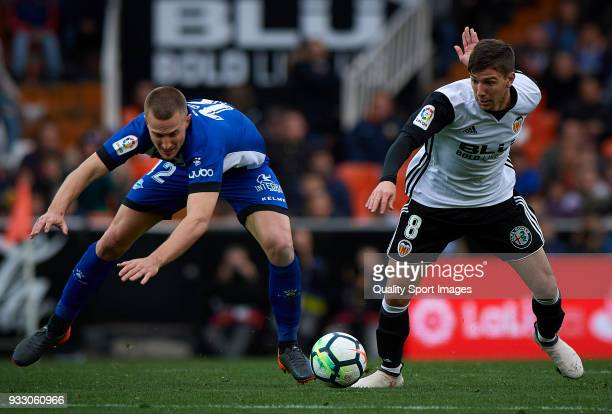 Luciano Vietto of Valencia competes for the ball with Rodrigo Ely of Alaves during the La Liga match between Valencia and Deportivo Alaves at...