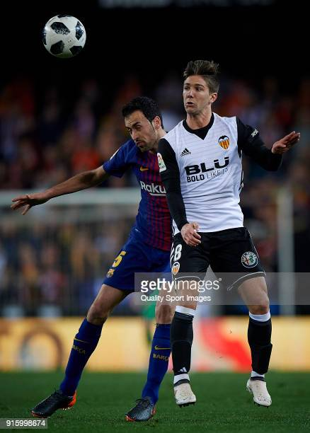 Luciano Vietto of Valencia competes for the ball with Sergio Busquets of Barcelona during the Semi Final Second Leg match of the Copa del Rey between...