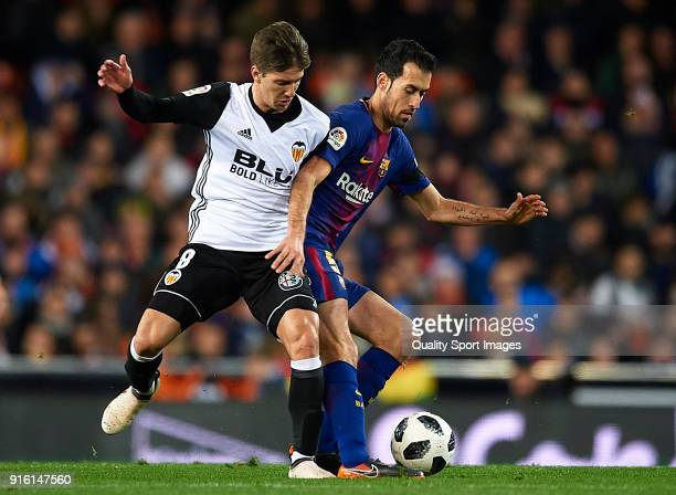 Luciano Vietto of Valencia competes for the ball with Sergio Busquets of Barcelona during the Copa del Rey semifinal second leg match between...